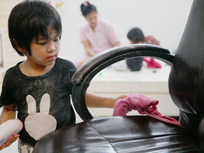 Weinig Aziatisch babymeisje die haar schoonmaken knoeit, lichaamspoeder, op leerstoel stock foto's