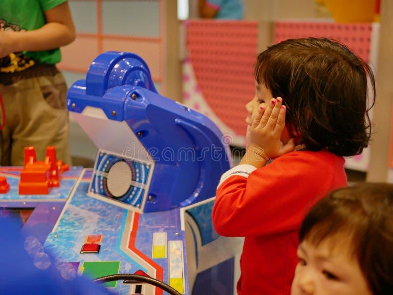 Weinig Aziatisch babymeisje gekregen dat over het arcadespel wordt opgewekt dat zij voor het eerst heeft gezien royalty-vrije stock foto