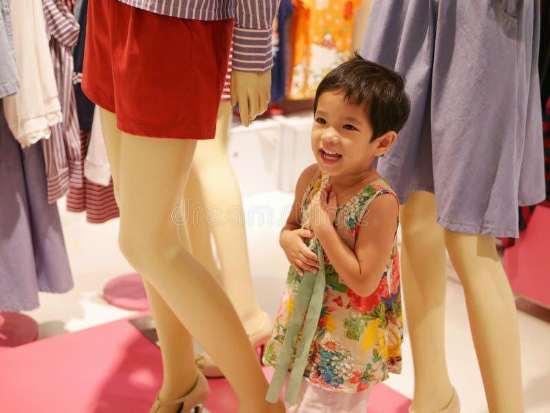 Weinig Aziatisch babymeisje geniet van bewerend aangezien zij één van de ledenpoppen die kleding in een winkelcomplex tonen is stock foto
