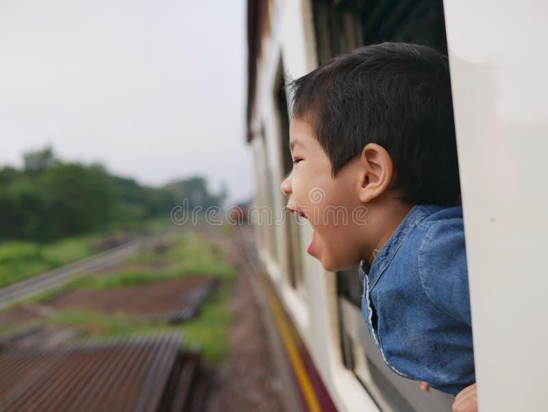 Weinig Aziatisch babymeisje geniet van schreeuwend van een treinvenster en het hebben van de wind ranselt tegen haar gezicht stock foto's