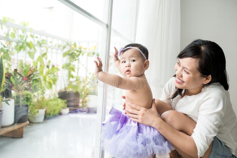 Weinig Aziatisch babymeisje thuis in witte ruimte bevindt zich dichtbij venster stock foto's