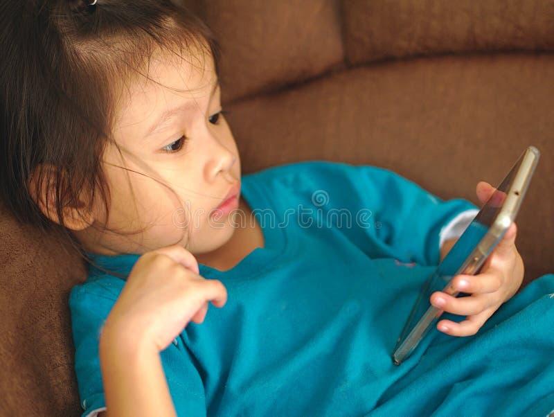 Weinig Aziatisch jong geitje die smartphone op bankbed gebruiken kijkt concentraat aan inhoud Het gebruiken van smartphone voor k stock afbeelding