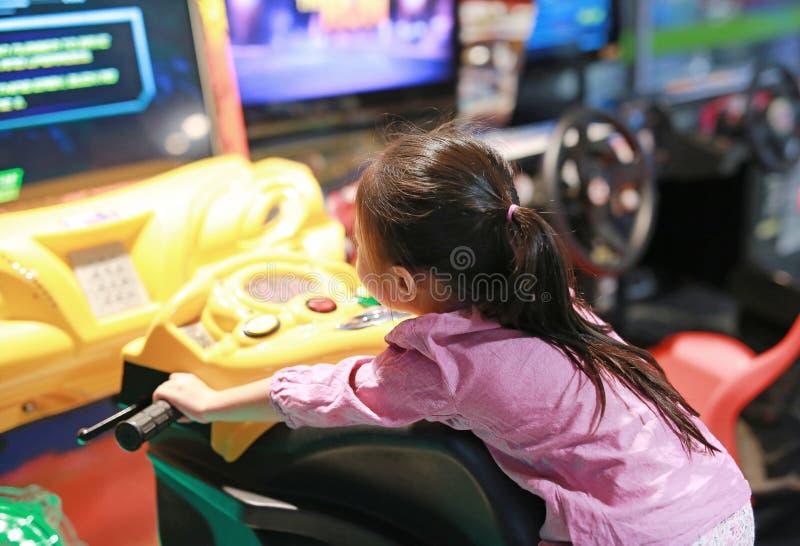 Weinig Aziatisch jong geitjemeisje het spelen arcadevideospelletje Motorfiets het Rennen stock foto's