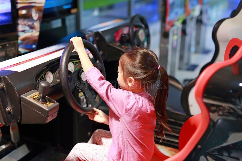 Weinig Aziatisch jong geitjemeisje het spelen arcadevideospelletje Het rennen auto stock foto