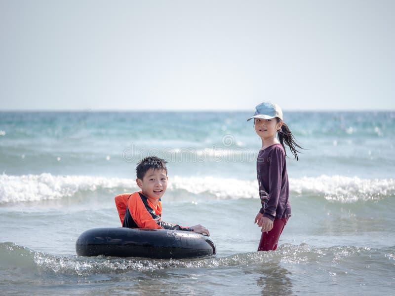 Weinig Aziatisch jongen en meisje spelen golven op het strand royalty-vrije stock foto