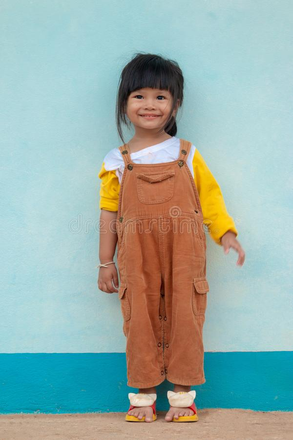 Weinig Aziatisch kind Leuk Aziatisch meisje in een bruine slabkleding die helder en pantoffels glimlachen dragen royalty-vrije stock afbeelding