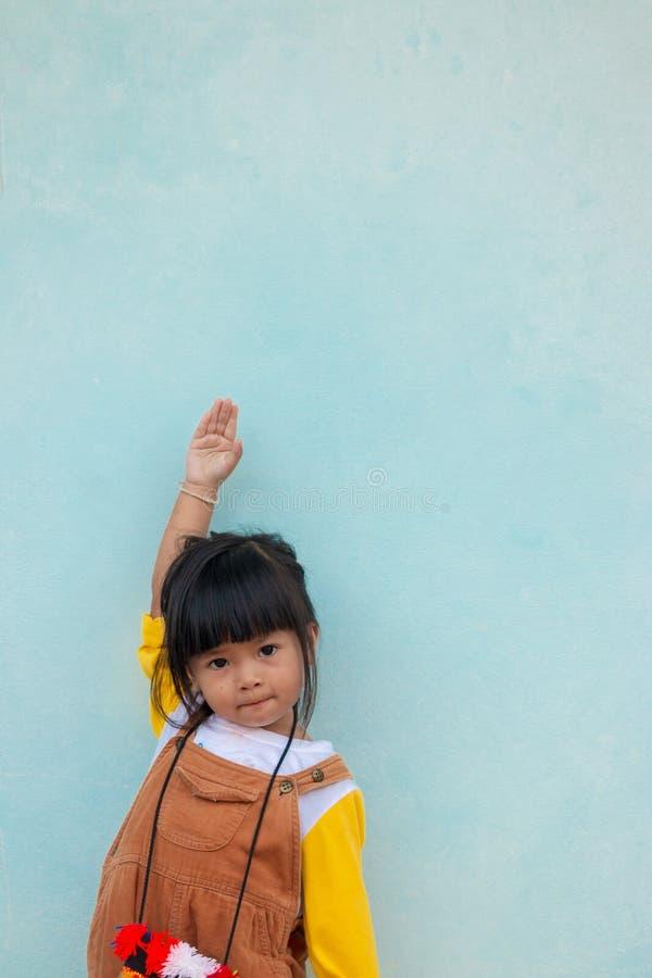 Weinig Aziatisch kind, Leuk Aziatisch meisje in een bruine slabkleding maakt rechts recht royalty-vrije stock foto's