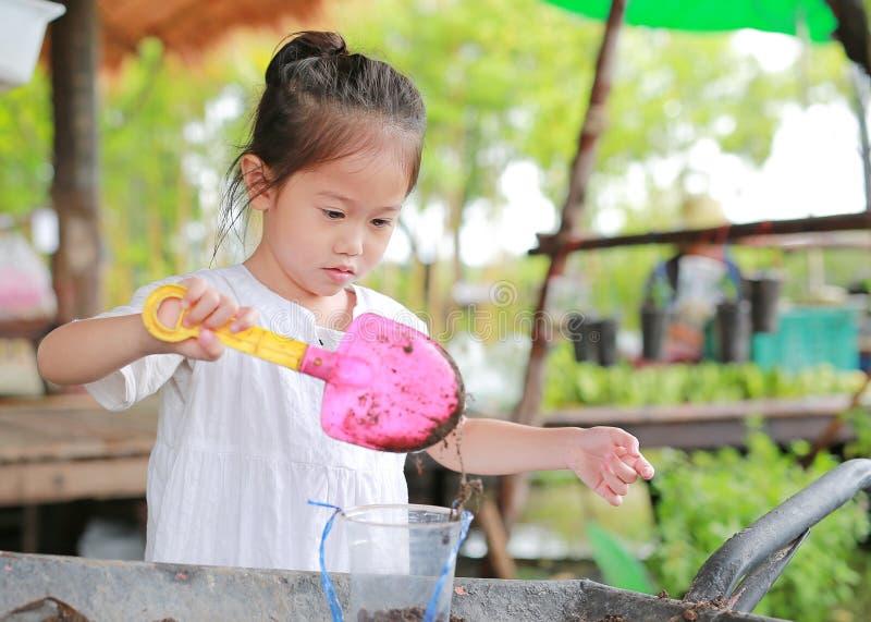 Weinig Aziatisch kindmeisje die de boom in pot planten royalty-vrije stock foto