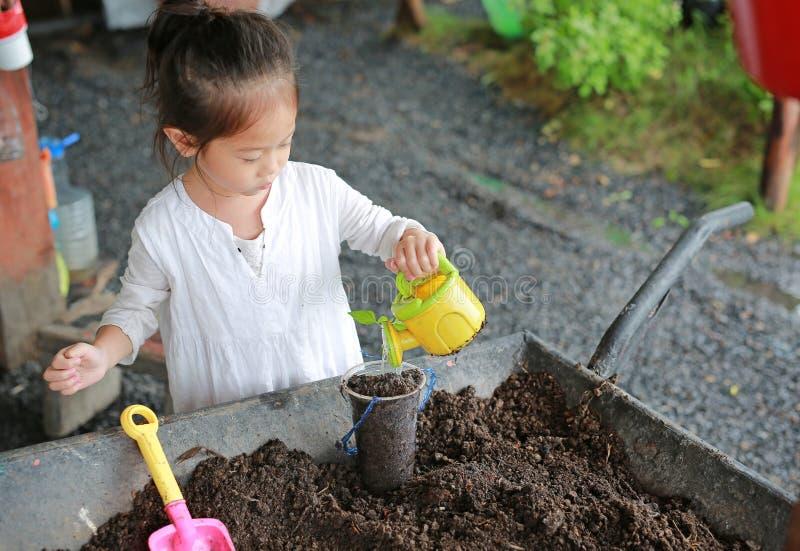 Weinig Aziatisch kindmeisje die de boom in pot planten stock afbeelding