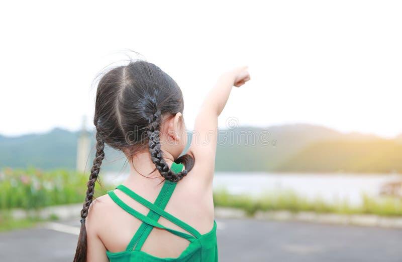 Weinig Aziatisch kindmeisje die op de zomergebied benadrukken openlucht Vrijheidsstijl openlucht stock afbeelding