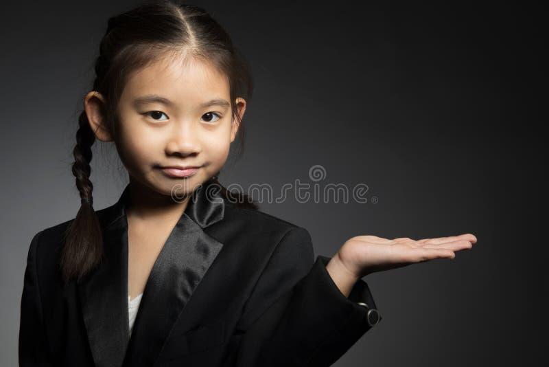 Weinig Aziatisch leuk meisje houdt handen uitgespreid het tonen van saldo royalty-vrije stock foto