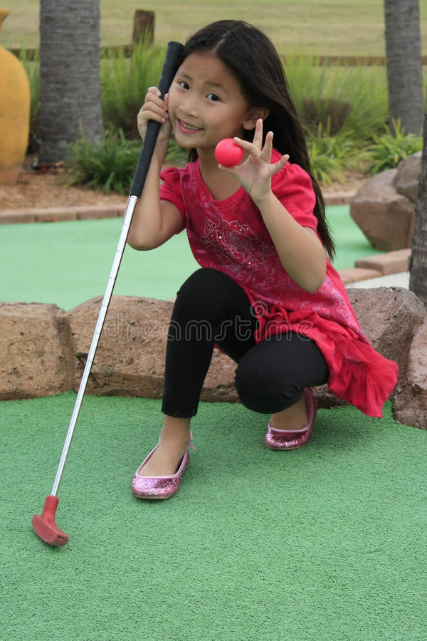 Weinig Aziatisch meisje dat minigolf speelt stock foto's