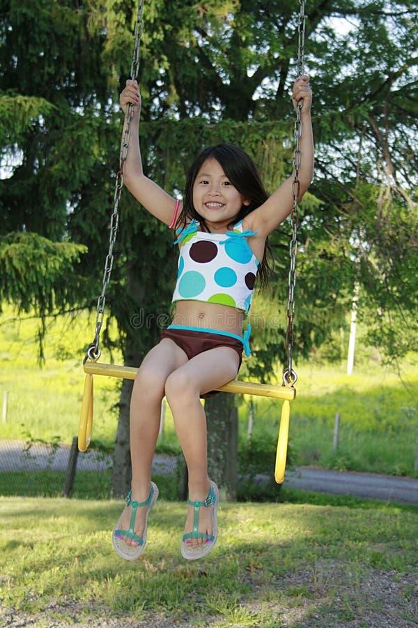 Weinig Aziatisch meisje dat op een schommeling slingert stock foto