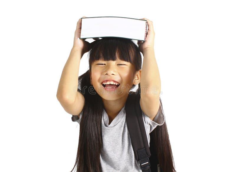 Weinig Aziatisch meisje die de boeken met haar rugzak houden stock afbeeldingen