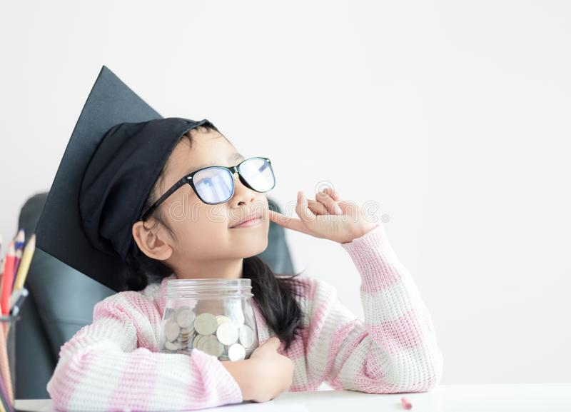 Weinig Aziatisch meisje die gediplomeerde hoed dragen die het duidelijke spaarvarken en de glimlach van de glaskruik met geluk di stock foto