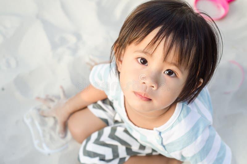 Weinig Aziatisch meisje die met zand spelen stock afbeeldingen