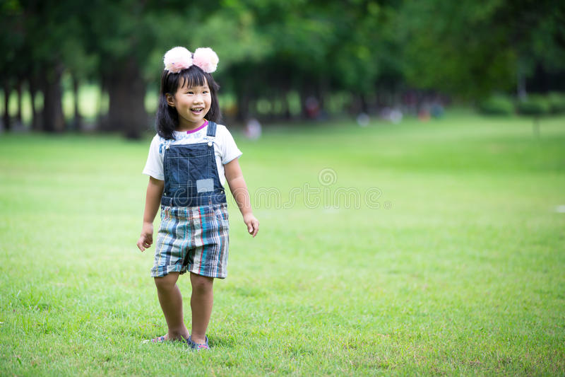 Weinig Aziatisch meisje die op groen gras bij het park spelen stock foto