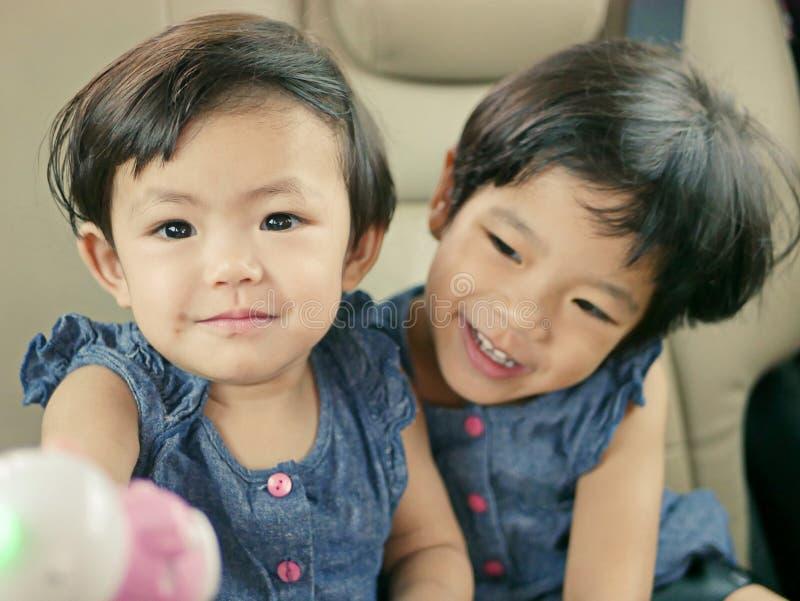 Weinig Aziatisch meisje die van de baby girLittle Aziatisch baby spelend een dollapop met haar oudere zuster genieten van stock afbeelding
