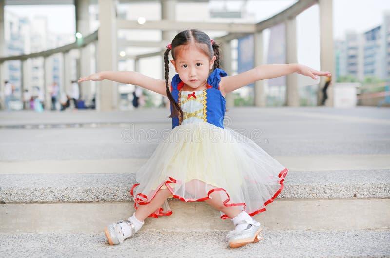 Weinig Aziatisch meisje kleedde zich met een zitting van het fantasiekostuum bij trede en uitgestrekte wapens stock afbeelding