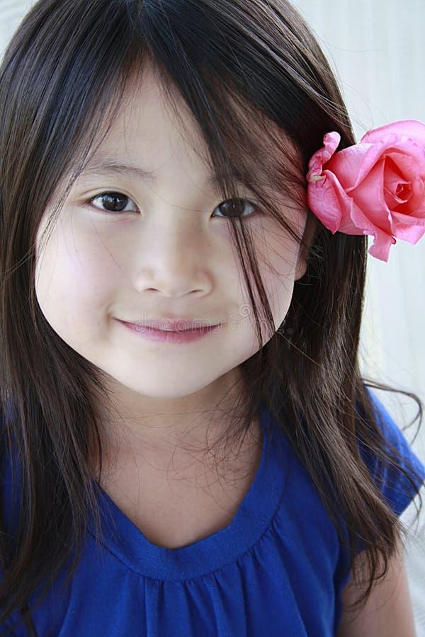 Weinig Aziatisch meisje met bloem in haar oor royalty-vrije stock foto's