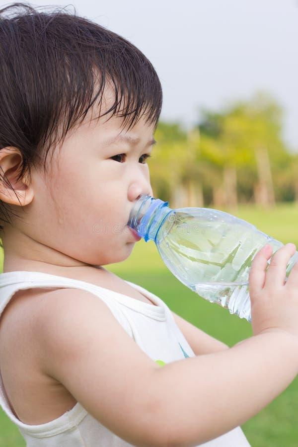Weinig Aziatisch meisjes drinkwater van plastic fles stock afbeelding