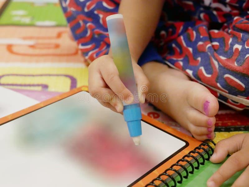Weinig Aziatische baby` s hand die grote kleurenpen houden om het schilderen te doen stock foto's