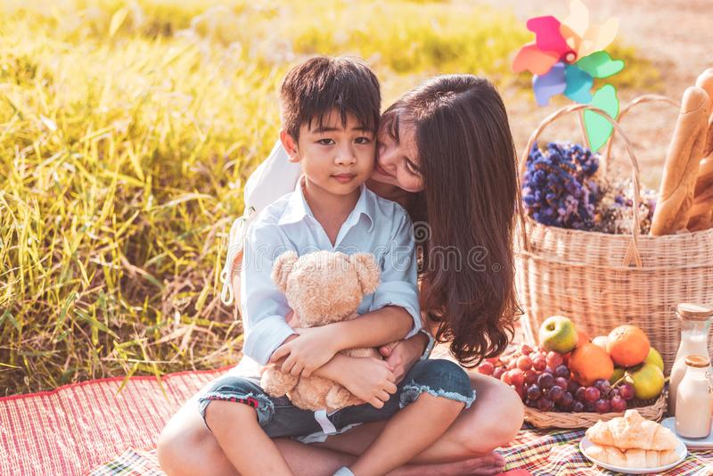 Weinig Aziatische die jongen bij wang door zijn mamma in weide wordt gekust wanneer het doen van picknick Moeder en Zoon die same stock afbeeldingen