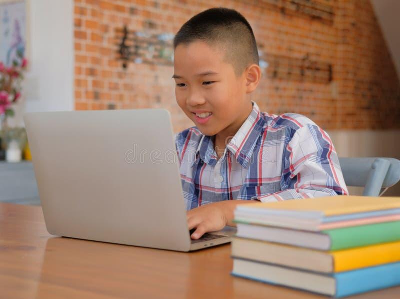 weinig Aziatische jong geitjejongen die doend thuiswerk bestuderen kind die les leren stock foto
