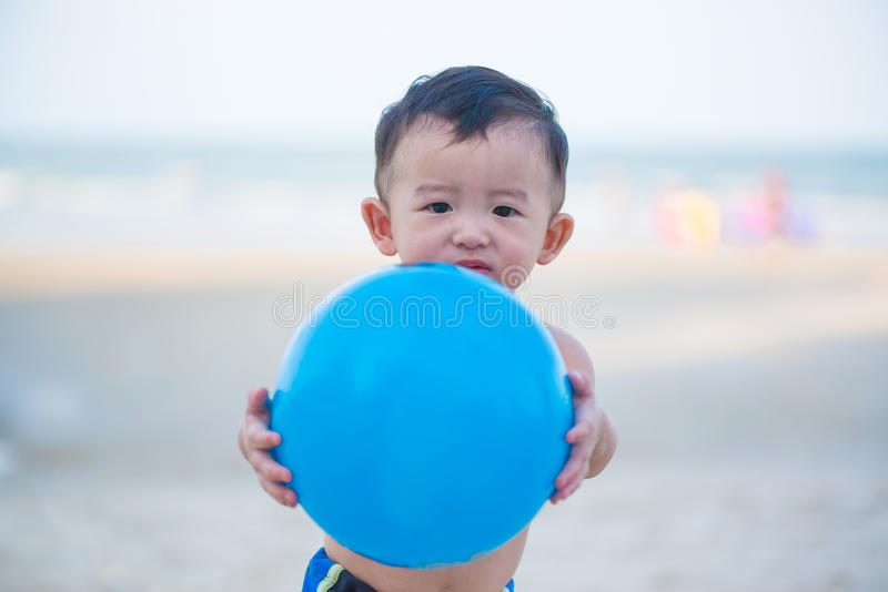 Weinig Aziatische jongen 1 éénjarige het spelen bal op het strand stock foto