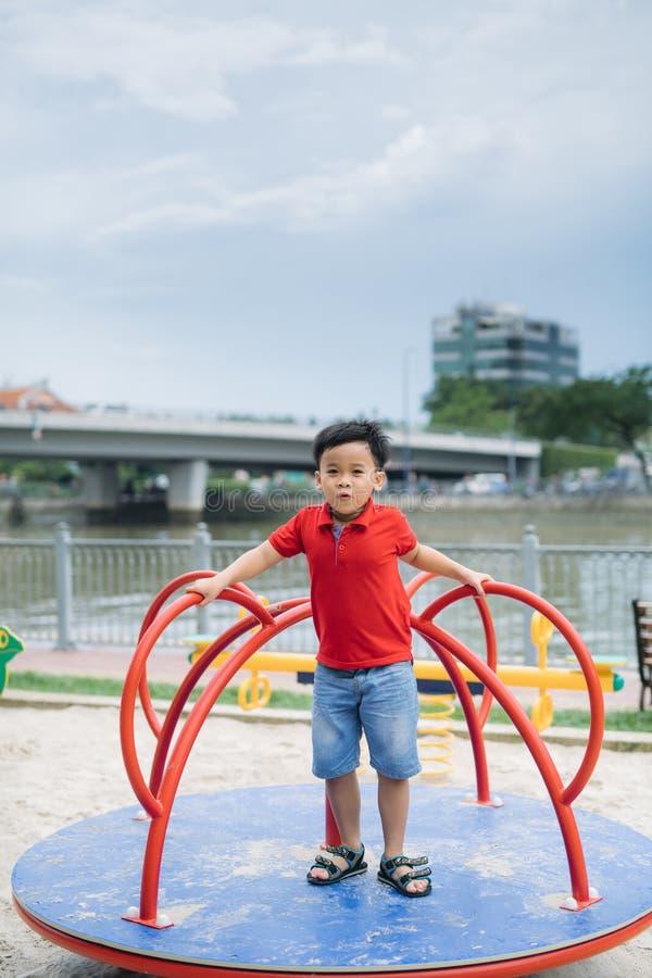 Weinig Aziatische jongen die een schommeling berijden en verheugt zich stock afbeelding