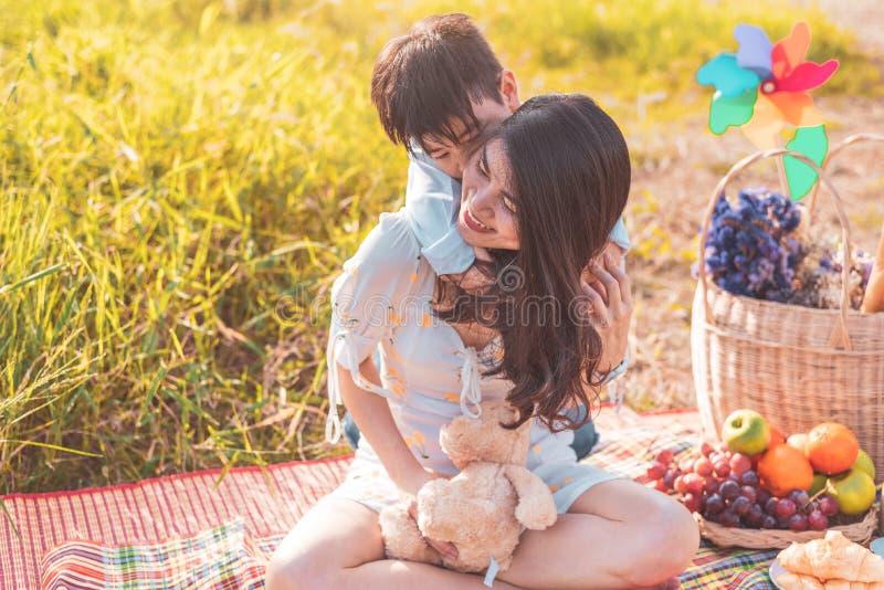 Weinig Aziatische jongen die terug op zijn super machtsmamma berijden in weide wanneer het doen van picknick Moeder en Zoon die s royalty-vrije stock foto
