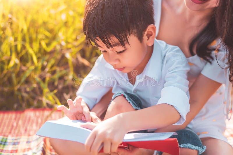 Weinig Aziatische jongen en zijn boeken van het het verhaalverhaal van de moederlezing bij weidegebied Moeder en zoon die samen l stock afbeeldingen