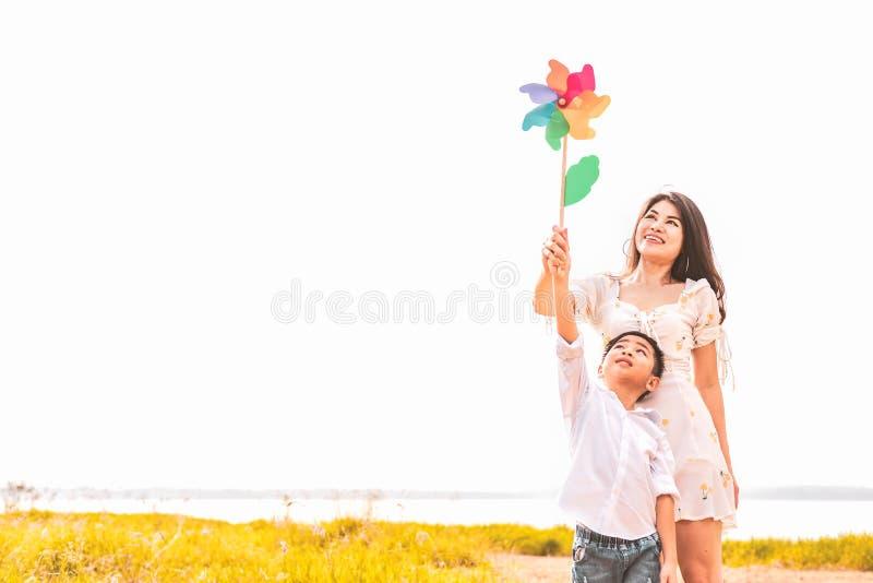 Weinig Aziatische jongen en zijn mamma die kleurrijke regenboogturbine in weide spelen Moeder en Zoon die samen spelen Het vieren stock foto's