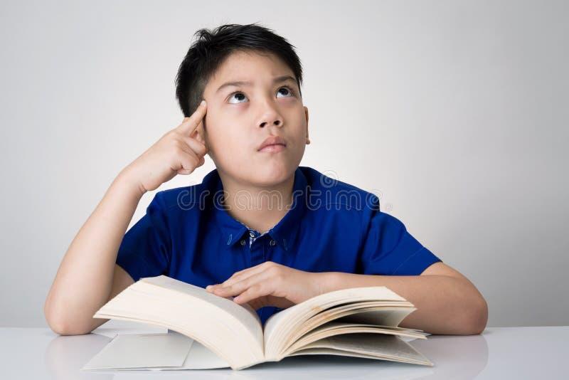 Weinig Aziatische jongen las een boek en denkt over dat royalty-vrije stock afbeelding