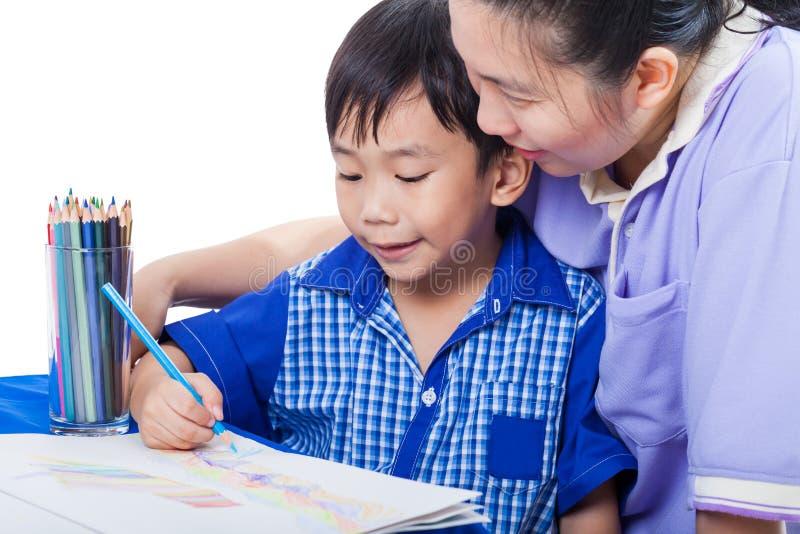 Weinig Aziatische jongenszitting bij de lijst en de tekening door kleur penc royalty-vrije stock afbeeldingen