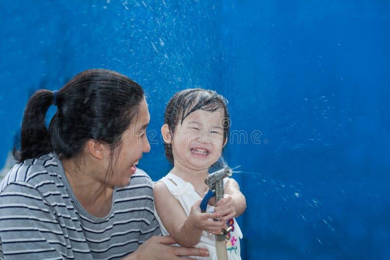Weinig Aziatische meisje en moeder spelen met waterslang royalty-vrije stock afbeeldingen