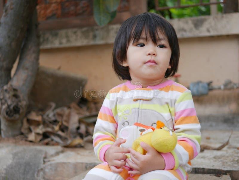 Weinig Aziatische zitting van het babymeisje met een gele eendpop royalty-vrije stock fotografie