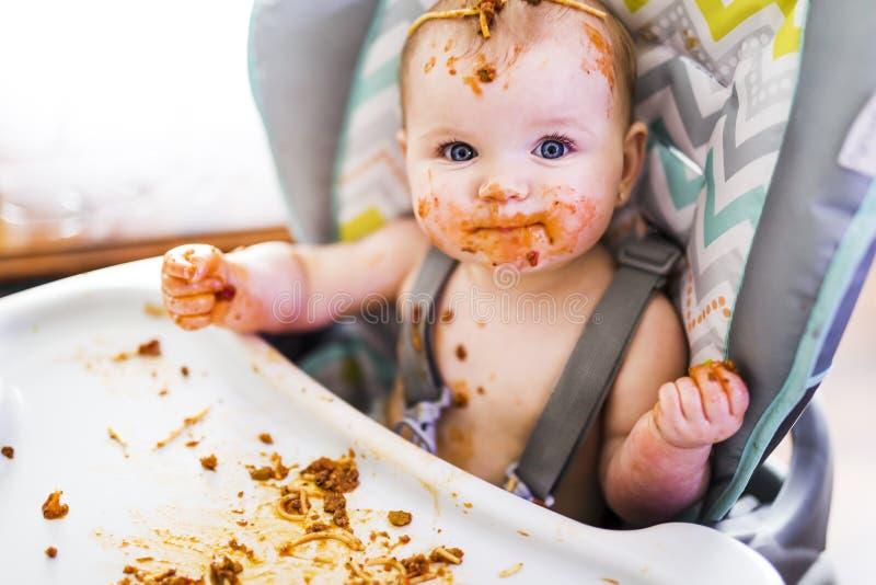Weinig baby die haar diner eten en maken knoeien stock foto's