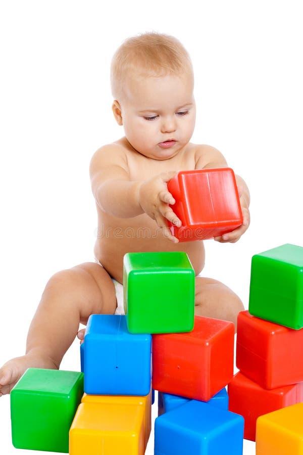 Weinig baby die met kubussen speelt stock foto's