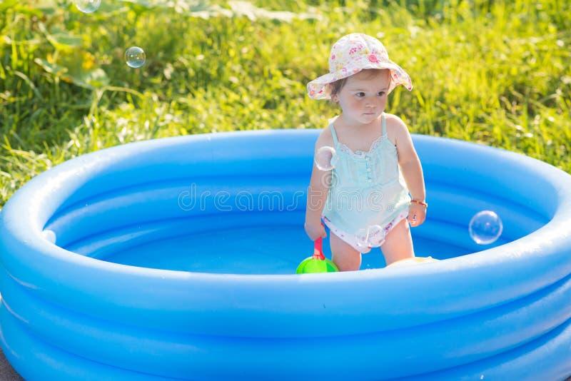 Weinig baby die met speelgoed in opblaasbare pool spelen stock afbeeldingen