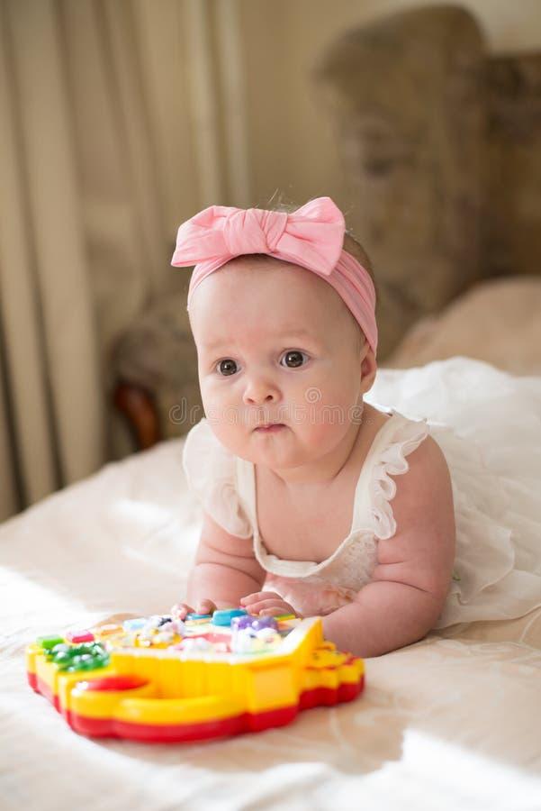 Weinig baby die met stuk speelgoed thuis spelen gelukkig kindmeisje die op bed in kinderdagverblijf leggen 8 van het babymaanden  stock foto