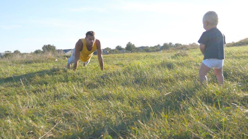 Weinig baby die zich op groen gras bij de weide bevinden en als zijn papa kijken die duw UPS doen Atletische mens die opdrukoefen stock foto's