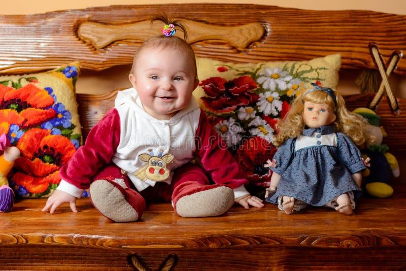 Weinig baby met een staart zit op een bank met geborduurd hoofdkussens en speelgoed stock afbeelding