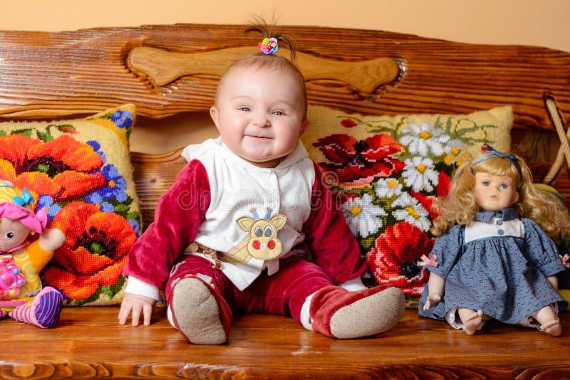 Weinig baby met een staart zit op een bank met geborduurd hoofdkussens en speelgoed royalty-vrije stock fotografie