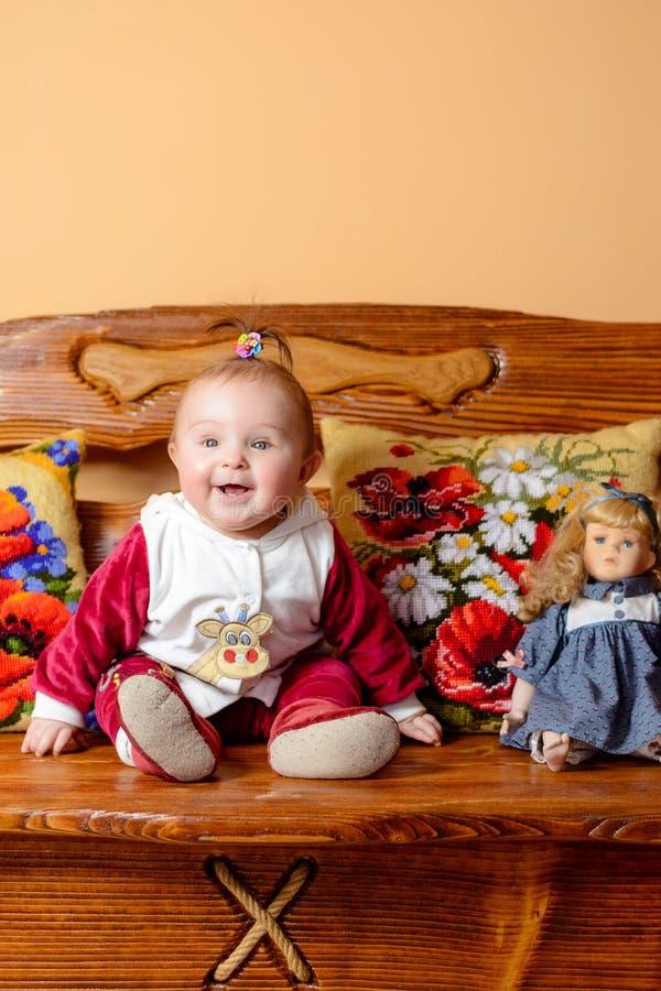Weinig baby met een staart zit op een bank met geborduurd hoofdkussens en speelgoed royalty-vrije stock afbeelding