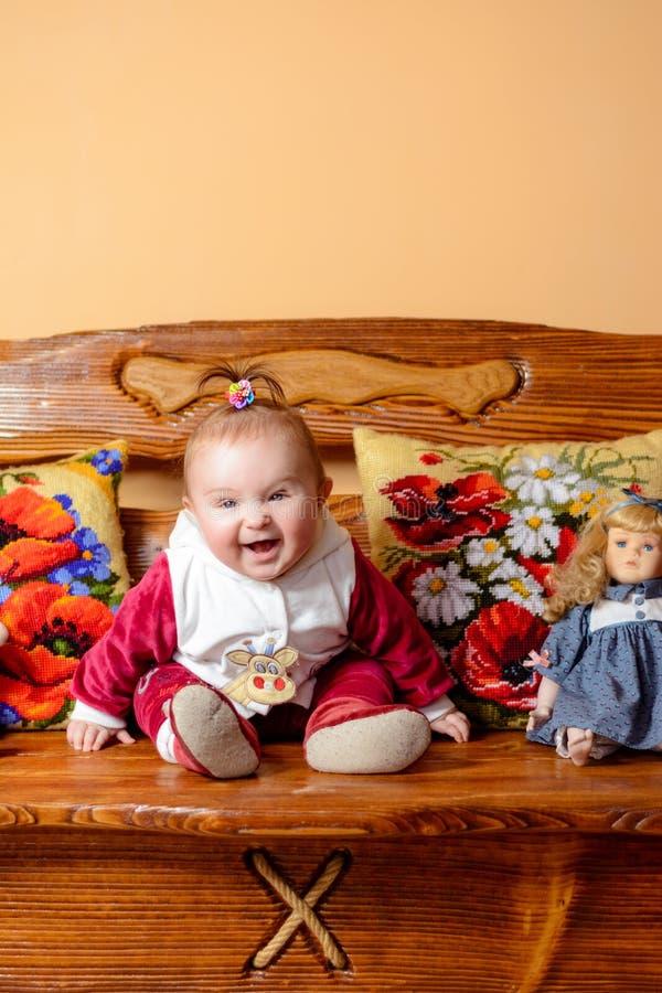 Weinig baby met een staart zit op een bank met geborduurd hoofdkussens en speelgoed royalty-vrije stock foto's