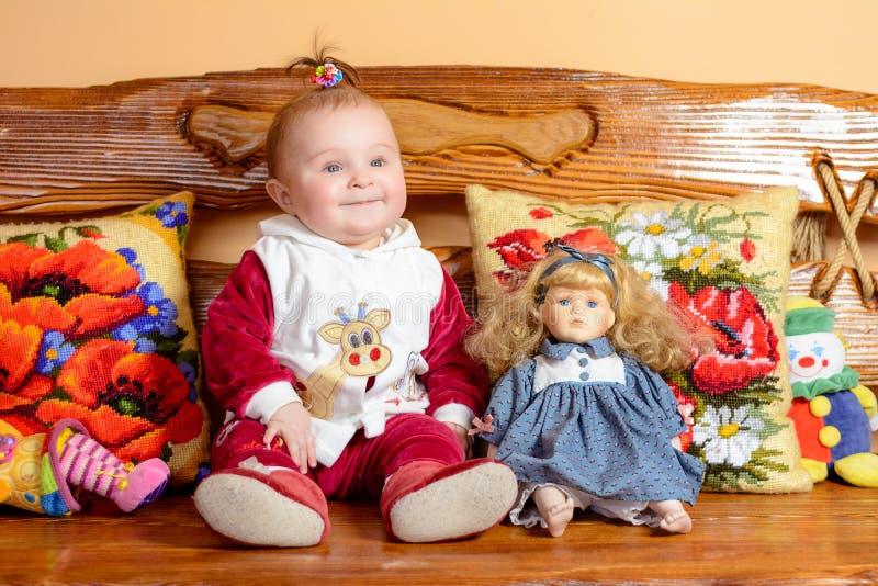 Weinig baby met een staart zit op een bank met geborduurd hoofdkussens en speelgoed stock fotografie
