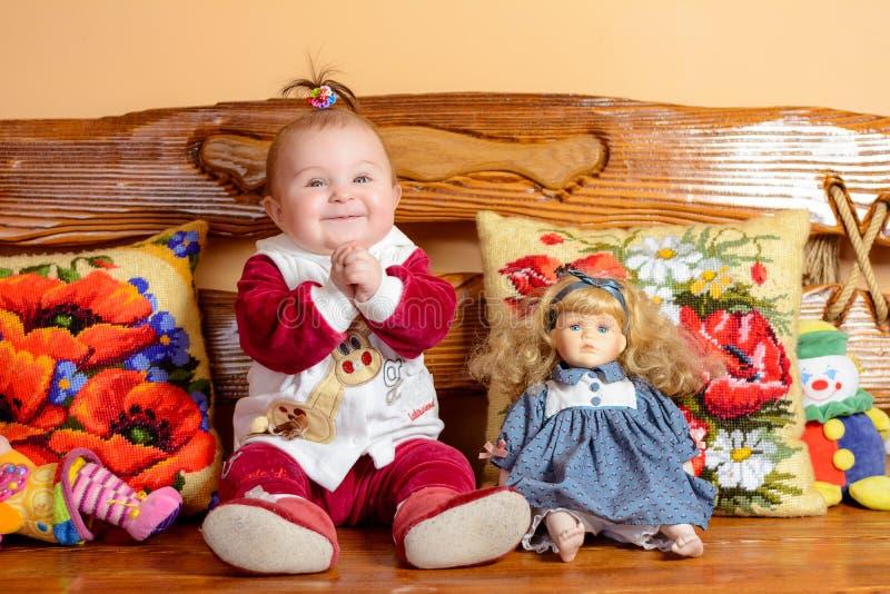 Weinig baby met een staart zit op een bank met geborduurd hoofdkussens en speelgoed royalty-vrije stock afbeeldingen
