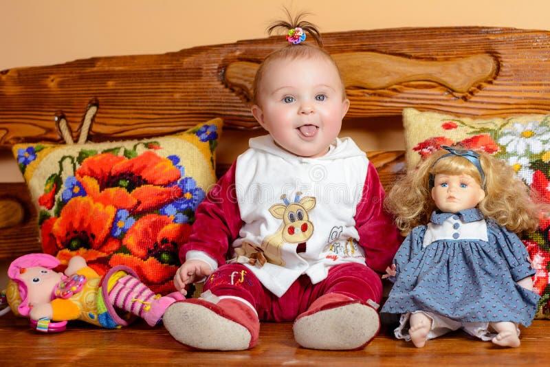 Weinig baby met een staart zit op een bank met geborduurd hoofdkussens en speelgoed stock foto