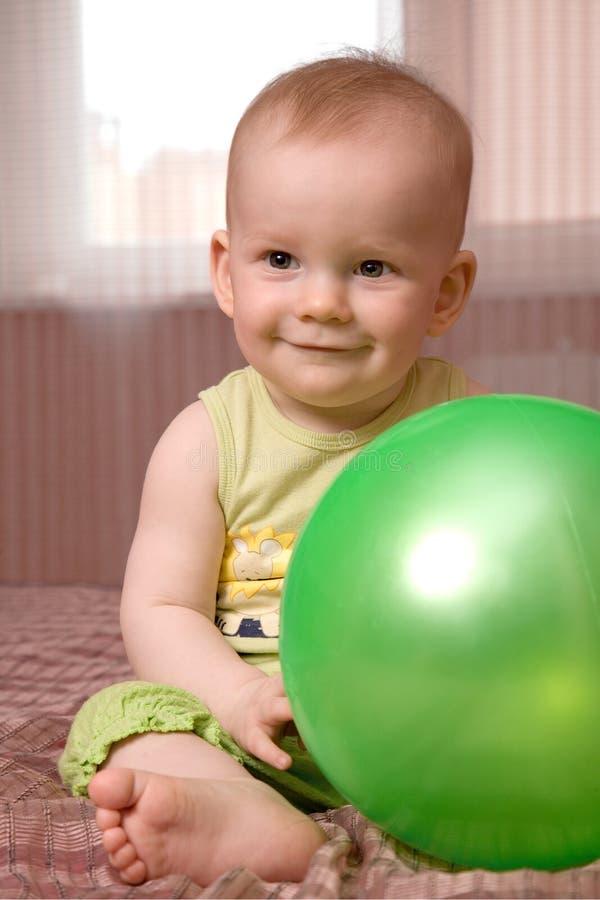 Weinig baby met groene bal stock foto